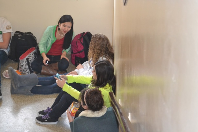 """A group of girls eats lunch together in the hallway. """"In a way, being a female or a minority adds to your confidence. You feel strong for being able to stand the discrimination,"""" Rebecca N. said."""