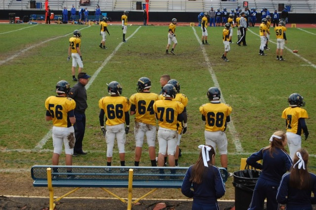 JV football player Jake Kollars (9), Drake Miller (9), John White (9), Michael Watson (10), Tommy Hutchins (10), Freeman Whitaker (9), and Anthony Amongero (10) stand on the sideline as they wait for their turn to get into the action against Brookville.