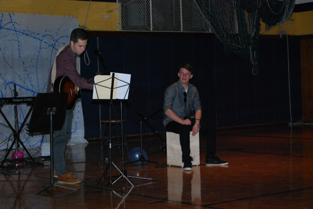 "Austin MacDonald (12) and Ben Baker (12) prepare to begin their set. The two seniors were the opening act for the benefit concert and performed songs such as ""Skinny Love"" by Bon Iver and ""Collide"" by Howie Day. Baker drummed along to MacDonald's acoustic guitar add bass tones to the performance."