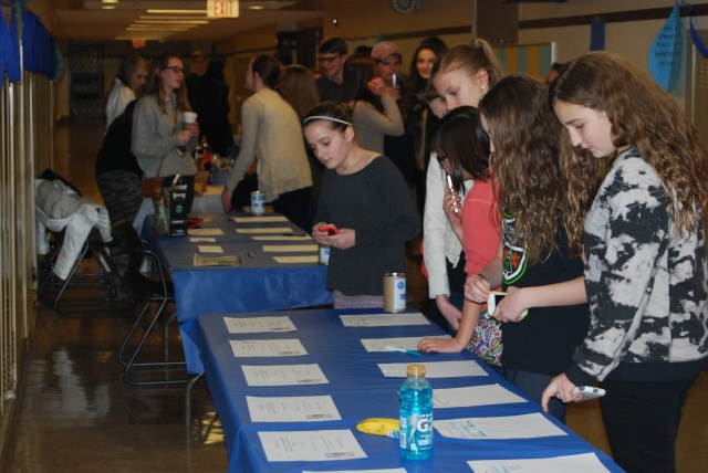 Students place bids at the concert's silent auction. After each performance, there was a ten minute break to participate in the auction and purchase food and drinks from the concession stand.