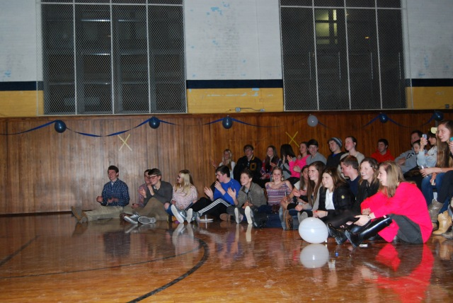 Students find seats on the floor of the West Gym to watch the performers. They sat on the ground because seats were hard to find after the concert commenced.
